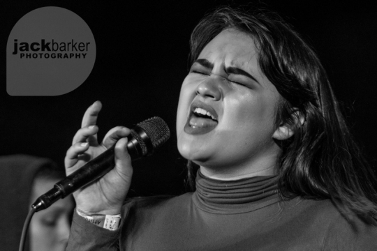 A female singer sings into a microphone with her eyes closed