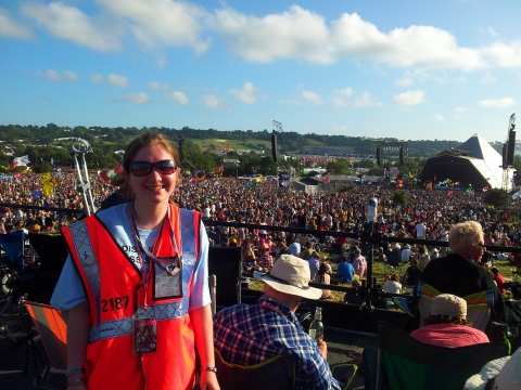 An Attitude is Everything volunteer stands on a viewing platform in front of the Pyramid stage at Glastonbury