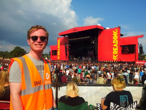 An Attitude is Everything volunteer stands on a viewing platform in front of the main stage at Reading Festival