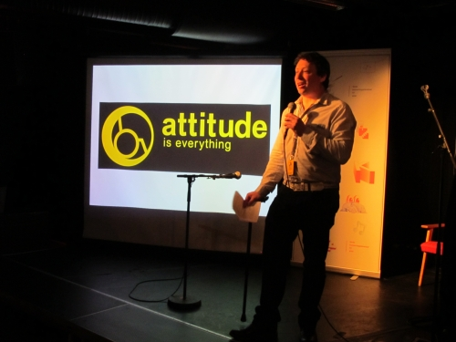 A man stands on a stage in front of the Attitude is Everything logo