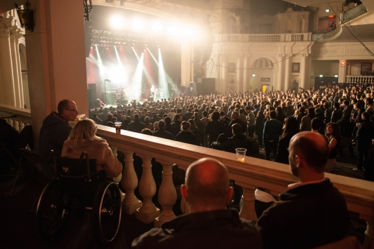 People watch a band at Brixton Academy from a viewing balcony