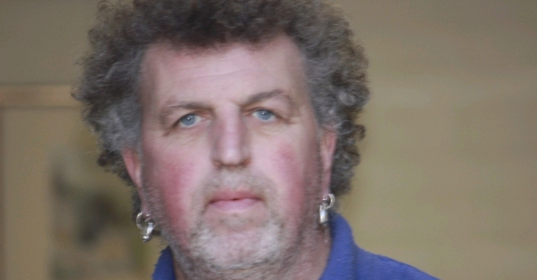 A photo of Paul Taylor, who has dark grey short curly hair, earings in each ear and wears a blue shirt