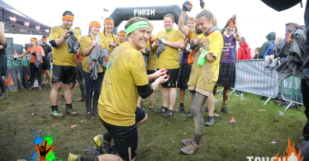 A proposal at the Tough Mudder finish line.