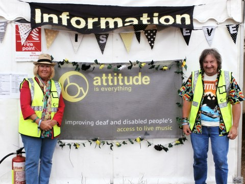 Two Attitude is Everything volunteers stand in front of an Information Tent