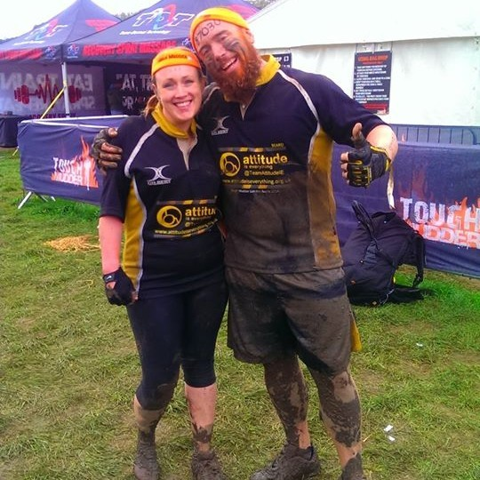 A man and a woman stand in front of a tent in running clothes covered in mud
